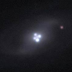 चारो नीले बिंदू एक ही क्वासर के चित्र है,इन क्वासर के सामने की एक आकाशगंगा के गुरुत्व से इस क्वासर की चार छवियाँ बन रही है।